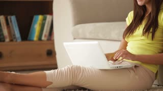 Beautiful girl sitting on floor with laptop and smiling at camera
