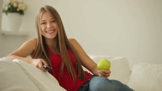 Beautiful girl sitting on sofa eating apple and holding remote control