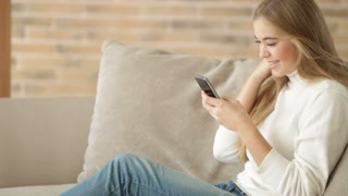 Beautiful girl sitting on sofa using mobile phone looking at camera and smiling. Panning camera