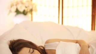 Beautiful girl sleeping in bed moving and smiling in her sleep. Panning camera