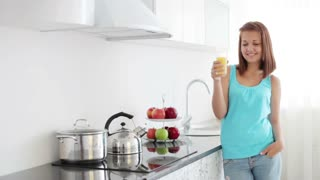 Beautiful girl standing in kitchen drinking juice and smiling