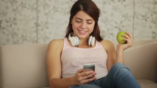 Beautiful girl wearing headset sitting on sofa eating apple using mobile phone looking at camera and smiling. Panning camera