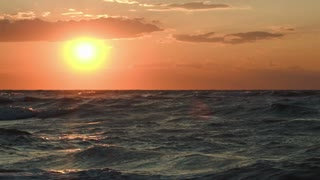 Beautiful golden sunset over sea with strong waves. Rough water in the evening sunlight