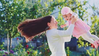 Beautiful happy mother spinning her baby at summertime outdoors in the garden. Happy parenthood and childhood concept. Slow motion filmed at 240 fps.