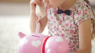 Beautiful little girl holding receiver talking on phone looking at camera and smiling