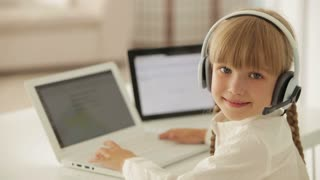Beautiful little girl in headset sitting at table working on laptop turning around and smiling at camera