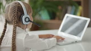 Beautiful little girl in headset with microphone sitting at table using laptop turning around and smiling at camera