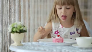Beautiful little girl sitting at cafe and eating cake