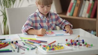 Beautiful little girl sitting at desk drawing with colored pencils and smiling at camera