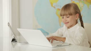 Beautiful little girl sitting at desk using laptop and touchpad and smiling at camera