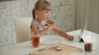 Beautiful little girl sitting at kitchen table eating chocolate sandwich drinking juice using touchpad and smiling at camera