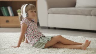 Beautiful little girl sitting on floor in living room listening to music on headset and smiling at camera
