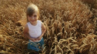 Beautiful little girl standing in wheat field smiling and waving her hand at camera