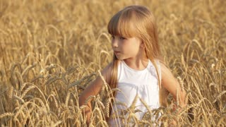 Beautiful little girl standing in wheat smiling and giving thumb up in slow motion