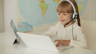 Beautiful little girl wearing headset sitting at table working on laptop and smiling at camera