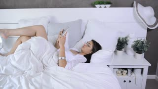 beautiful modern brunette woman using tablet computer in luxury white bedroom