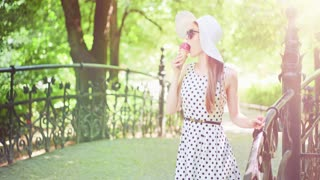 Beautiful woman eating ice cream in the park. Slow motion. Stylish young attractive woman in white hat and dress enjoying tasty ice cream and nature in the green sunny summer outdoors. 4K, DCi.