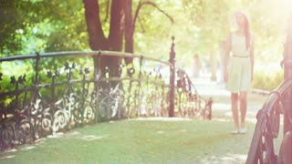 Beautiful woman in the park. Elegant lady relaxing in the green garden outdoors on a decorative bridge, looking around then turning to the camera and smiling. Slow motion, 4K, dci. Summer time.