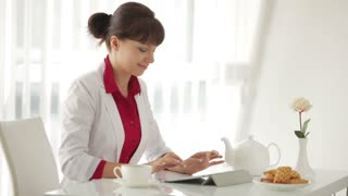 Beautiful woman sitting at table with cup of tea and using tablet
