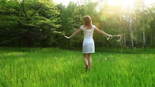 Beautiful woman spinning in the grass. Dolly HD
