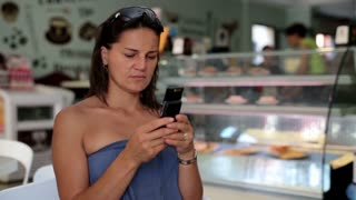 Beautiful woman texting message on mobilephone and drinking coffee in restaurant