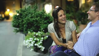 Beautiful young couple sitting on bench in city night, steadicam shot