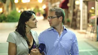 Beautiful young couple walking in city night, steadycam shot