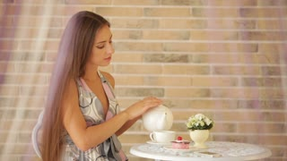 Beautiful young girl sitting at cafe and pouring tea into cup