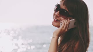 Beautiful young woman in bikini talking smart phone on the sea beach. Sunny summer by the sea. Slow motion. Filmed at 250 fps.