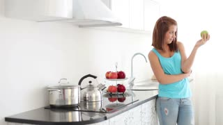 Beautiful young woman in kitchen holding apple and smiling