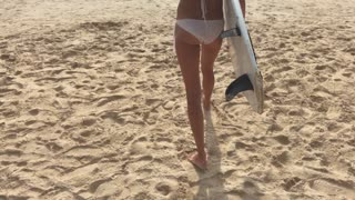 Beautiful young woman in white swimsuit with surfboard walking down at sea beach