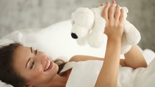 Beautiful young woman lying in bed playing with teddy bear and smiling at camera. Panning camera