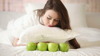 Beautiful young woman lying in bed with apples in front of her looking at camera  laughing and smiling. Panning camera