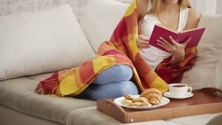 Beautiful young woman relaxing on sofa with tray of food reading book closing it and smiling at camera. Panning camera