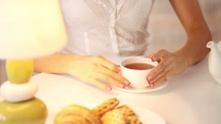 Beautiful young woman sitting at cafe drinking tea looking at camera and smiling. Panning camera