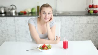Beautiful young woman sitting at kitchen table with bowl of salad and glass of juice in front of her and smiling at camera