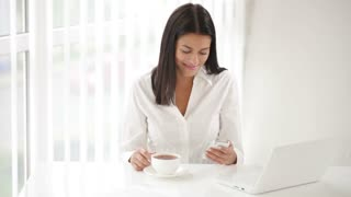 Beautiful young woman sitting at office desk holding cup of tea using cellphone looking at camera and smiling