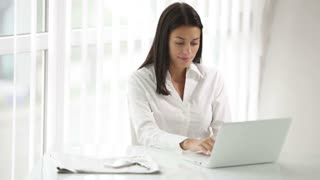 Beautiful young woman sitting at office desk using laptop looking at camera and smiling