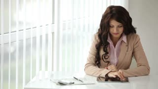 Beautiful young woman sitting at office table using touchpad and smiling at camera