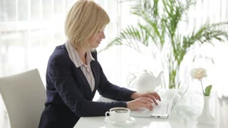 Beautiful young woman sitting at office table working on laptop looking at camera and smiling