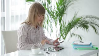 Beautiful young woman sitting at table holding mobile phone in her hand using touchpad and smiling at camera