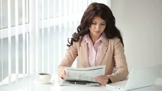 Beautiful young woman sitting at table reading newspaper stirring coffee and smiling at camera