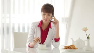 Beautiful young woman sitting at table with cup of tea and talking on cellphone