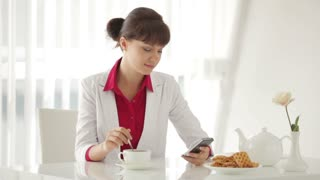 Beautiful young woman sitting at table with cup of tea and using cellphone