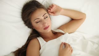 Beautiful young woman sleeping in bed and smiling in her sleep