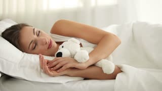 Beautiful young woman sleeping in bed hugging teady bear and smiling in her sleep