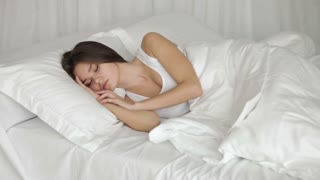 Beautiful young woman sleeping in bed moving and smiling in her sleep