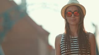 Beautiful Young Woman smiling in the European city, cinematic portrait. Slow Motion, 4K. Happy Hipster girl enjoying the sun and the life. Travel in style. Lens flare.