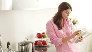 Beautiful young woman standing in kitchen using touchpad and smiling