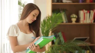 Beautiful young woman standing with paper folders writing in notebook and smiling